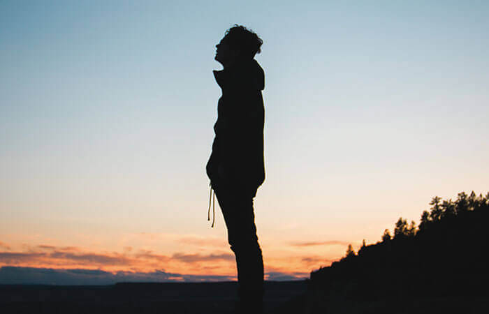 夕日の野原に一人寂しく立つ男性